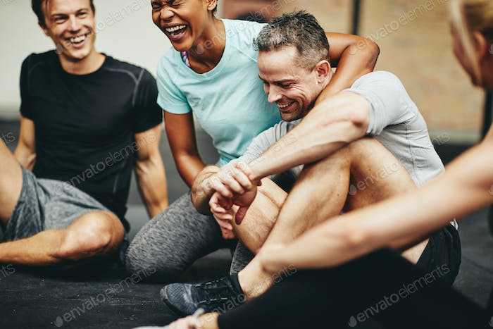 Diverse friends sitting in a gym laughing together after exercising