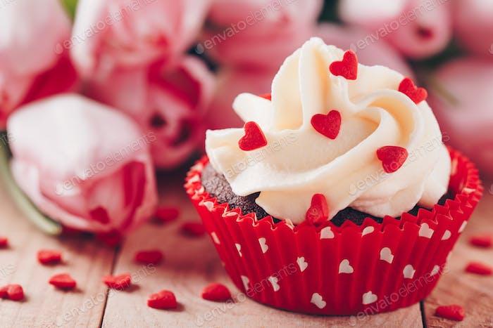 Schokoladen-Cupcake mit Vanillecreme und roten Zuckerherzen zum Valentinstag