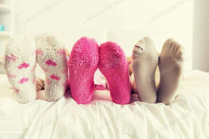 close up of women feet in socks on bed at home