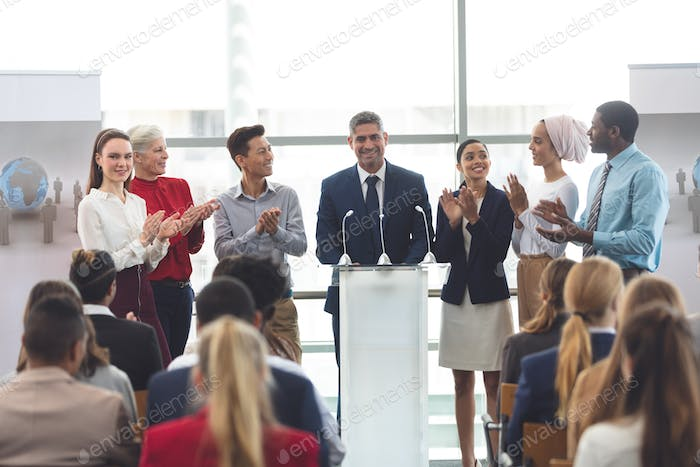 Diverse business professionals standing on podium while speaking at a business seminar in office