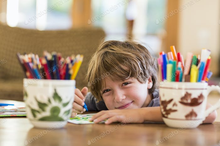 6 year old boy drawing amoung colorful pens