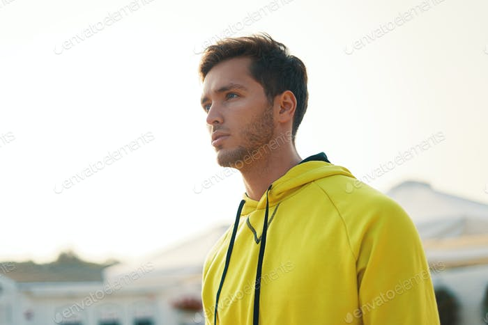 Thoughtful young man in yellow hoodie portrait