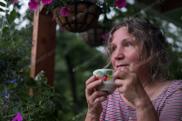 Senior woman in green garden with flowers in hands