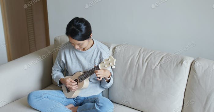 Frau spielen mit Ukulele zu Hause