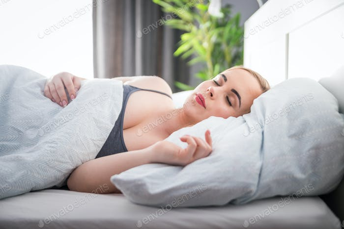 Natural woman peacefully sleeping in bed on soft pillow