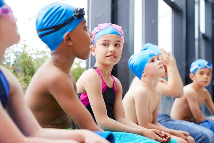 Group Of Children Sitting On Edge Of Pool Waiting For Swimming Lesson