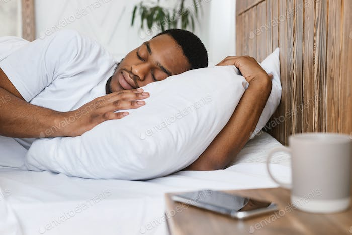 African Guy Sleeping Through Alarm-Clock Lying In Bed At Home