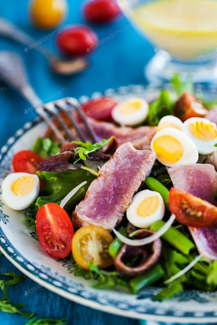 Tuna salad with tomatoes, boiled eggs, onion, anchovy and lettuc
