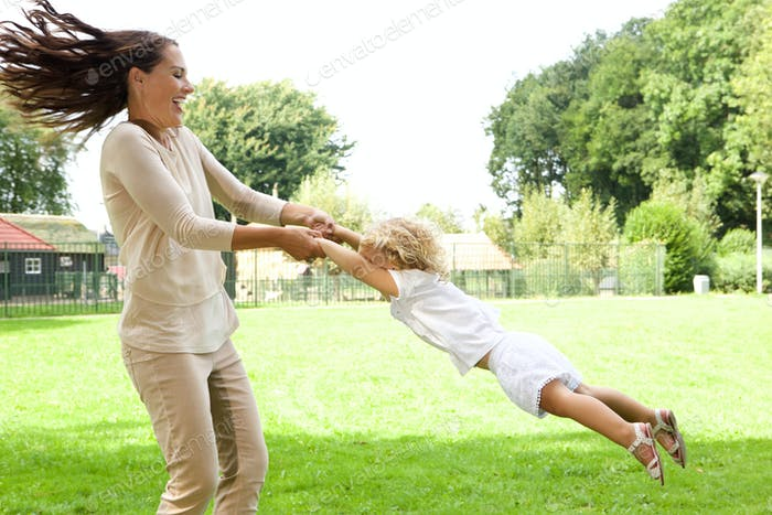 Young mother swinging daughter in the park