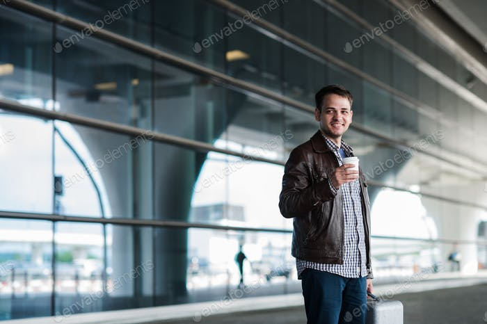 Stylish handsome young male traveller with bristle standing outdoors. Man wearing jacket and shirt
