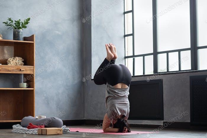 Woman practicing yoga near window in headstand exercise, salamba sirsasana