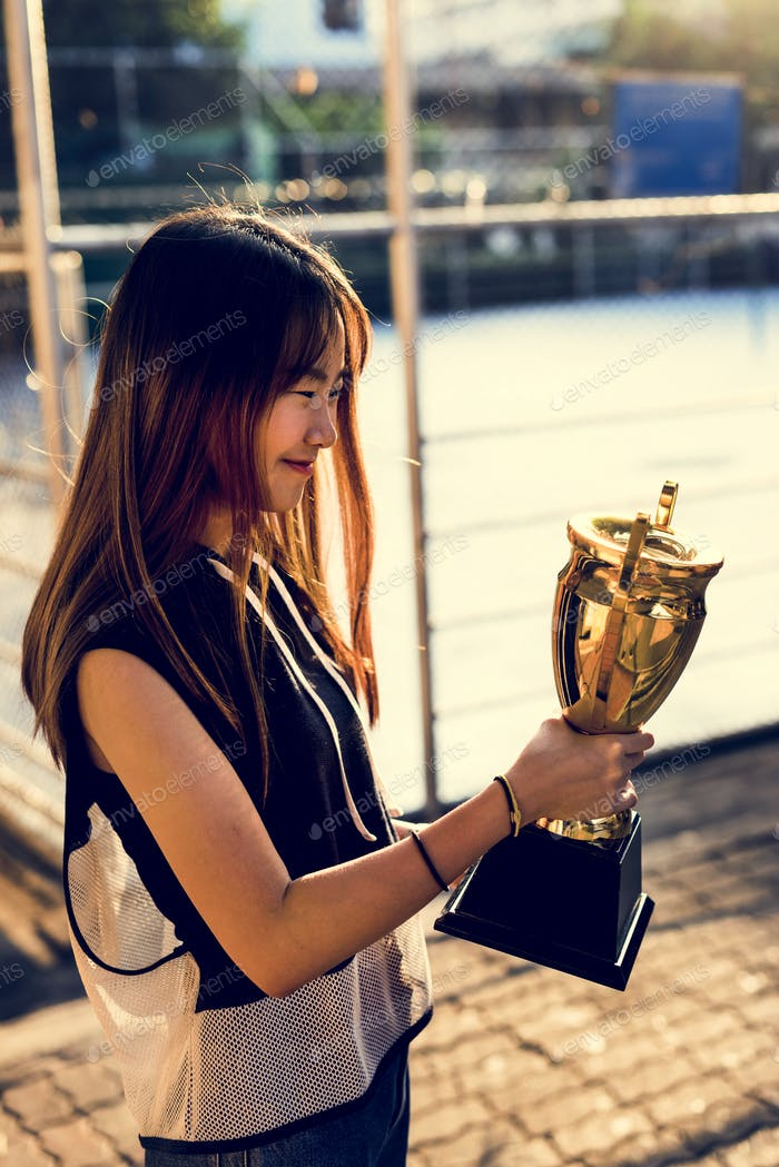 Asian teenage girl in sporty clothes holding a trophy outdoors