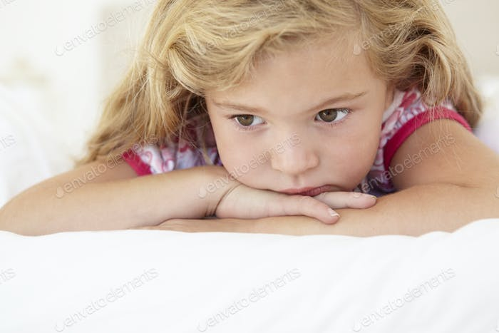 Young Girl Looking Sad On Bed In Bedroom
