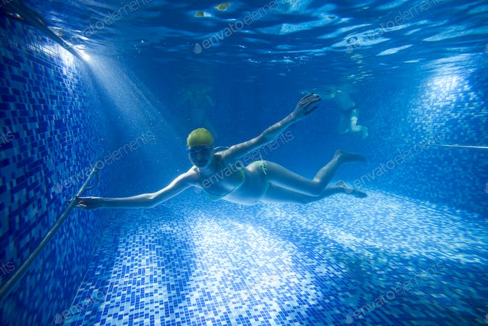 Young pregnant woman underwater in swimming pool