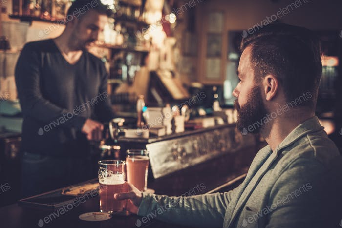 Stilvoller Mann allein an der Bar mit einem Pint leichtem Bier sitzen.