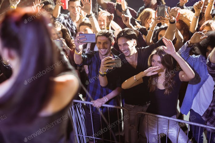 Cheerful young crowd photographing performer at nightclub