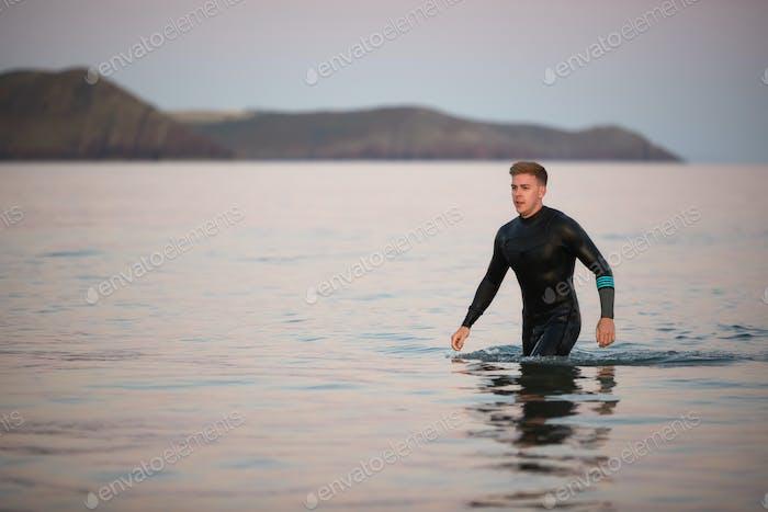 Mann tragen Neoprenanzug waten durch flache Meer durch Shore