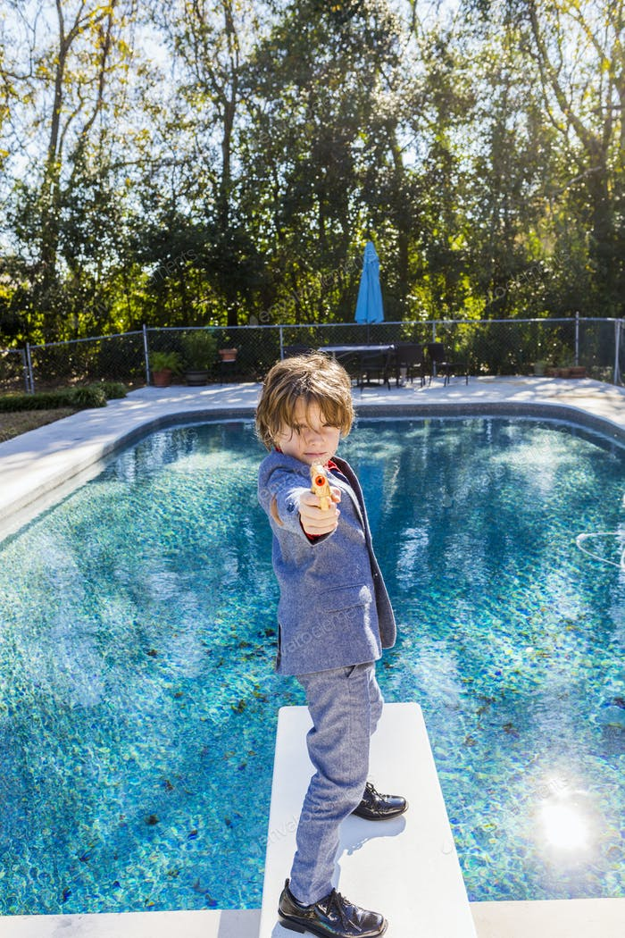 6 year old boy standing on diving board overlooking pool