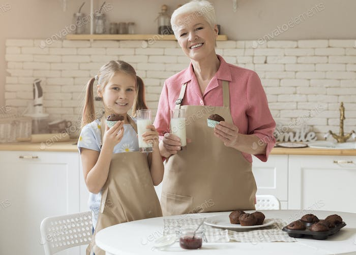 Cheerful grandmother and her lovely granddaughter with fresh muffins and milk in kitchen