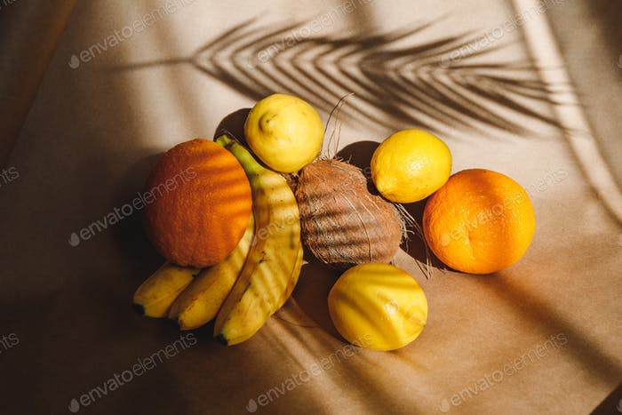Creative summer food still life with bananas, coconut, oranges and lemons