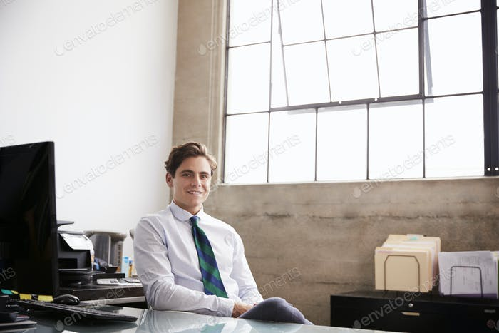 Young white businessman sitting in office smiling to camera