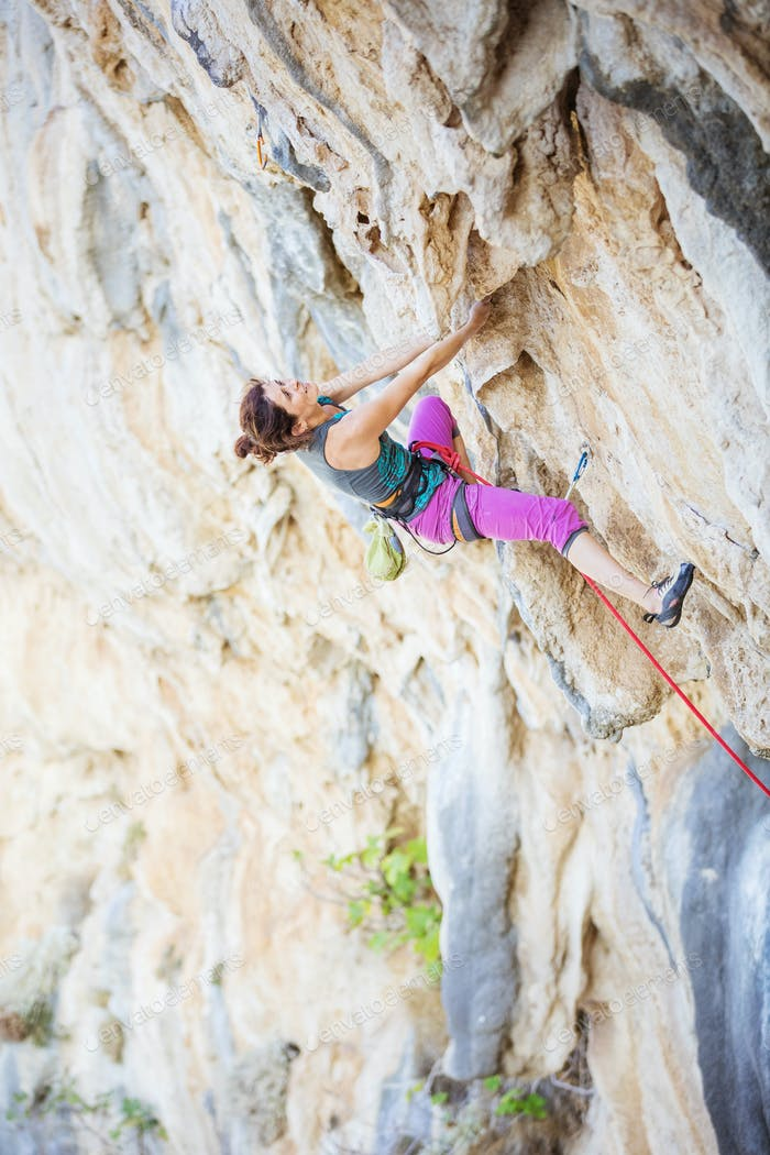 Young woman climbing challenging route on overhanging cliff