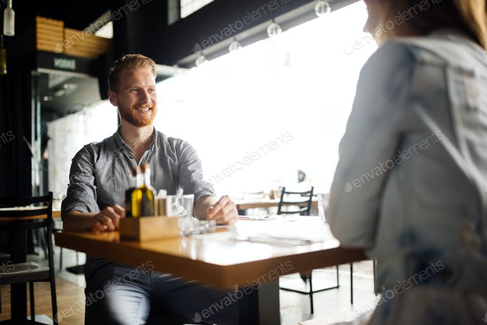 Beautiful man and woman flirt in cafe