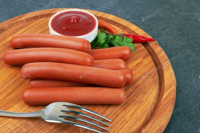 Raw frankfurter sausages with ketchup