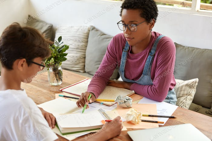Tutoring, education and encouragement concept. Serious black female tutor conducts geometry class wi