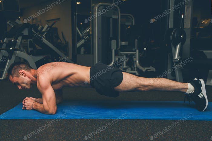 man doing plank position at the gym