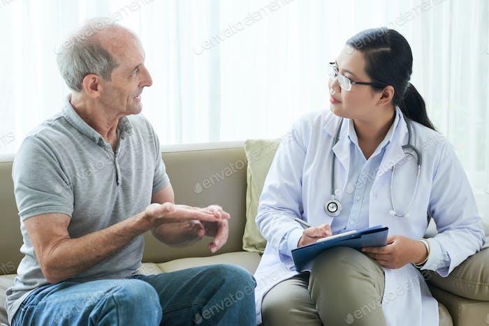 Senior man talking to doctor on sofa at home
