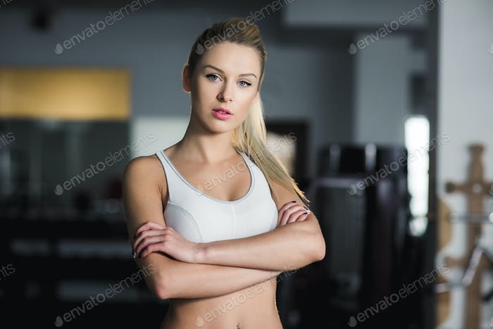 Beautiful athletic girl  poses in the gy