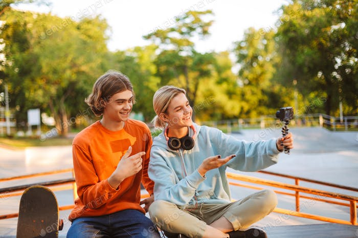 Young skater boy and girl with headphones happily recording new