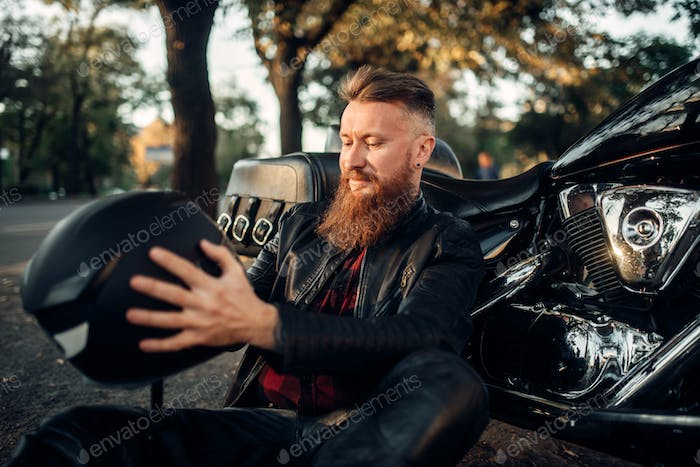 Biker sitting on the ground against his chopper