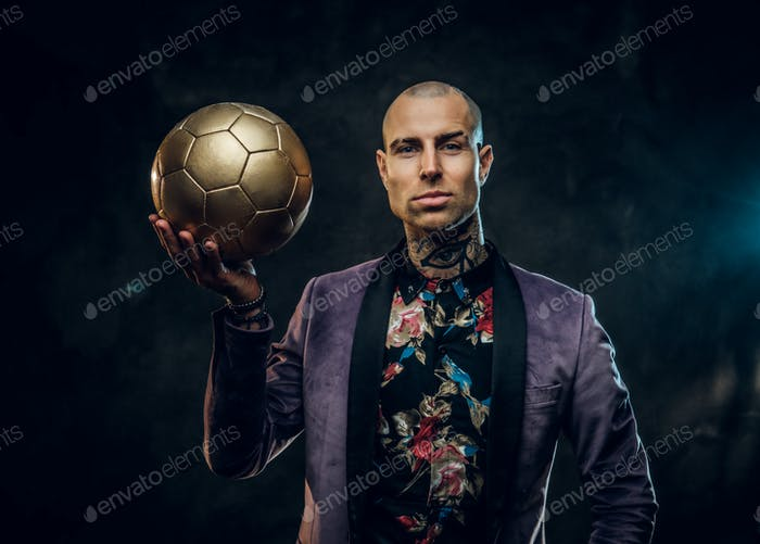 Elegant tattooed male model posing with a golden soccer ball in a studio