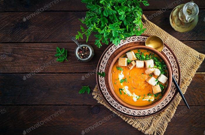 Kürbissuppe in einer Schüssel serviert mit Croutons und Petersilie