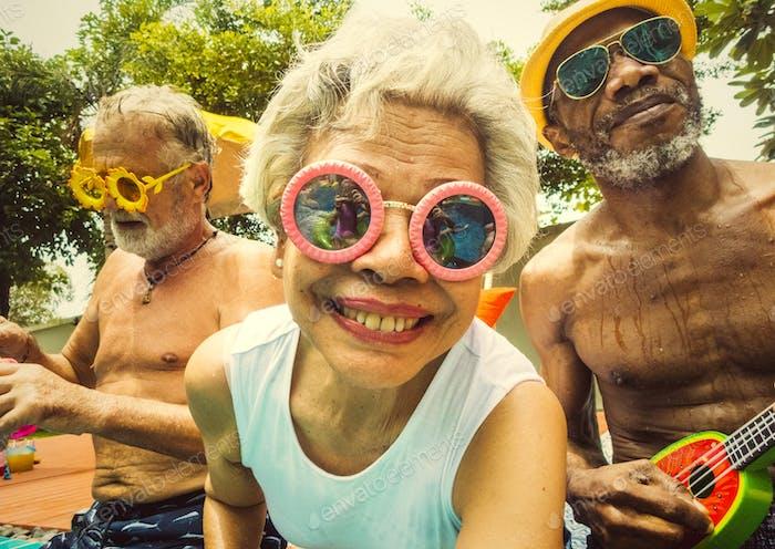 Nahaufnahme von verschiedenen Senioren sitzen am Pool genießen su