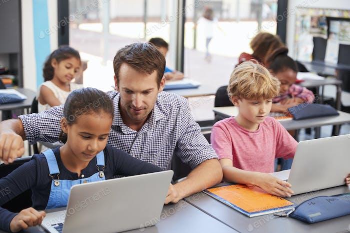 Lehrer hilft jungen Schülern mit Laptops im Unterricht