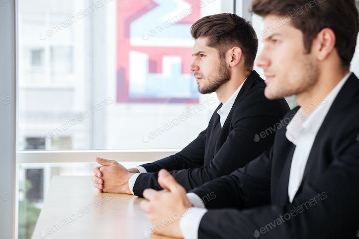 Two concentrated young businessmen sitting in office