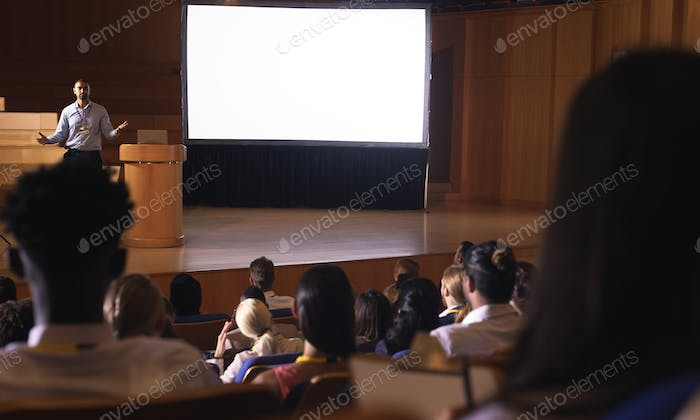 Audience listening to the presentation while businessman giving presentation in auditorium