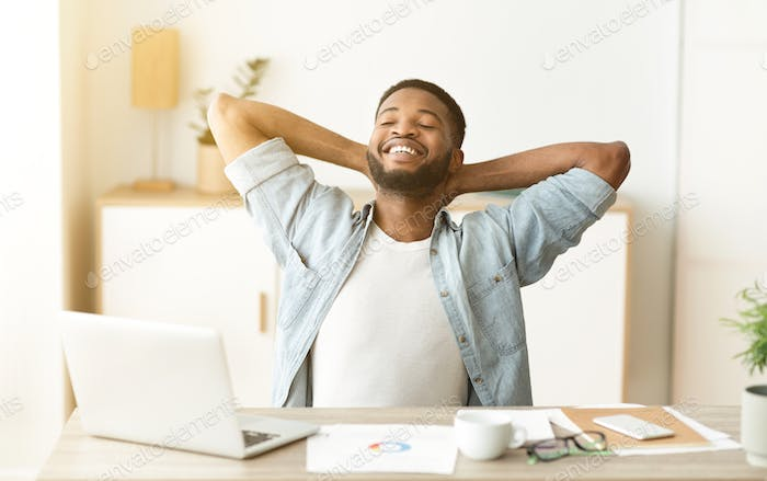 Happy afro worker leaning back in chair after successful workday