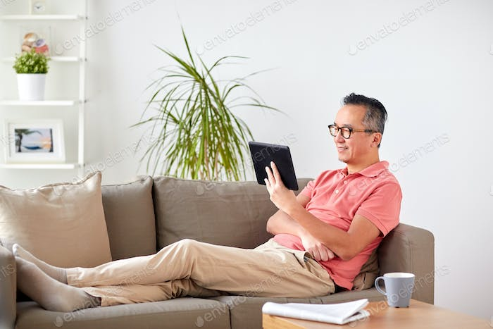 man with tablet pc sitting on sofa at home