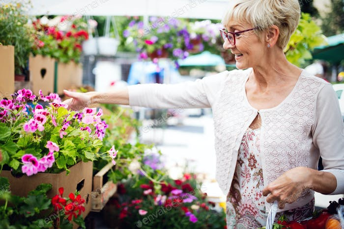 Beautiful senior woman selecting flowers at market