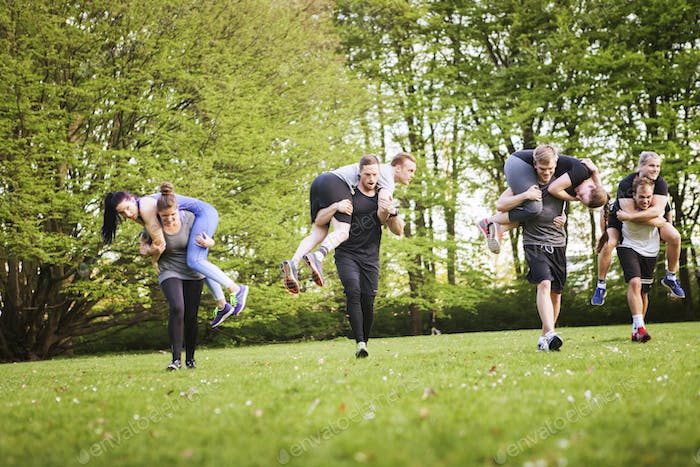 Man and woman carrying friends while running on field