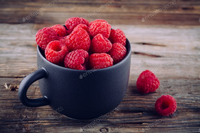Fresh ripe organic raspberry in a mug on a wooden background