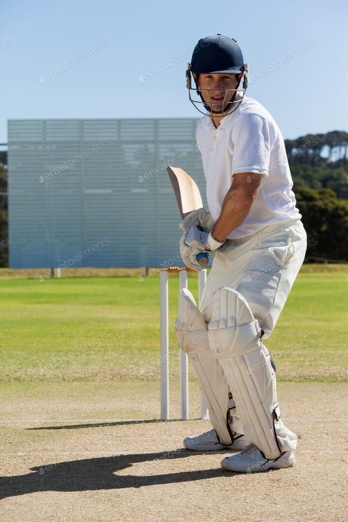 Concentrated player playing cricket on field against clear sky