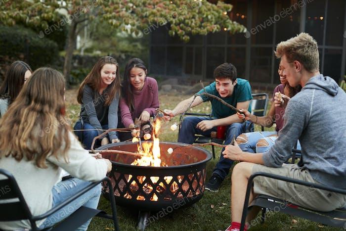 Teenager-Freunde sitzen um eine Feuerstelle Toast Marshmallows