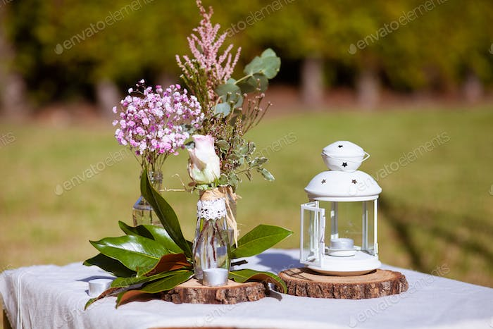 Outdoors wedding decoration with flowers and a lantern