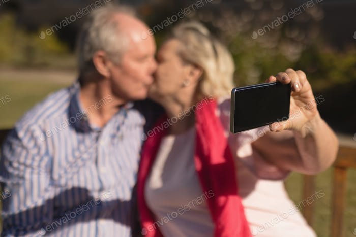 Senior couple taking selfie with mobile phone while kissing each other in the park