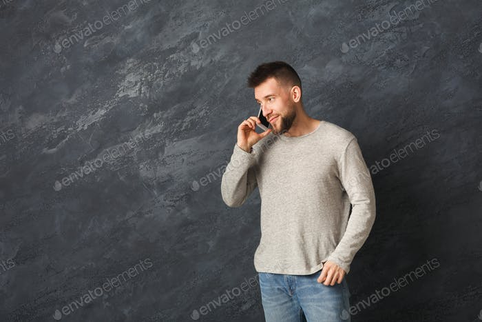 Smiling man talking on smartphone in studio